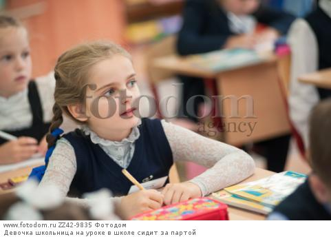 Девочка школьница на уроке в школе сидит за партой