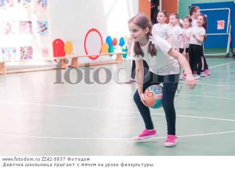 Девочка школьница прыгает с мячом на уроке физкультуры