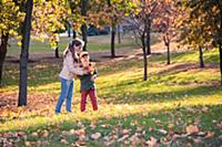 Мальчик и девочка гуляют в парке осенью в солнечны