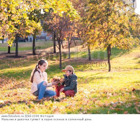 Мальчик и девочка гуляют в парке осенью в солнечный день