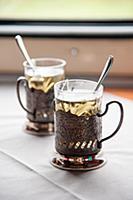 Стаканы в металлических подстаканниках с чаем у ок