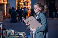 Девушка в сером пальто с книгой в руках на улице г